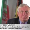 Minister Laumann vor den Fahnen von EU, Deutschland und NRW