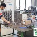 Foto: Bildungsscheck für Geflüchtete – Ein junger Mann steht an einem Arbeitstisch