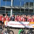 """Minister Laumann steht mit den Teilnehmenden der """"Radtour Pro Organspende"""" vor dem Haupteingang des Ministeriums. Sie halten ein Schild mit der Aufschrift Minister Laumann mit den Teilnehmenden der """"Radtour Pro Organspende"""""""