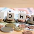 """Vier Würfel liegen auf Euro-Münzen. Sie bilden das Wort """"Lohn""""."""
