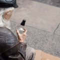 Alter Mann sitzt auf der Straße und blickt auf eine Flasche in seiner Hand