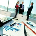 Foto: Gespräch Geschäftspartner_in - Vordergrund: Laptop, Statistikauswertungen