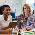 Pflegekraft mit Migrationshintergrund bei Besprechung mit zwei Kolleginnen