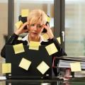 Foto zeigt gestresste Frau vor einem Aktenberg