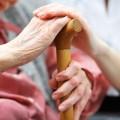 Foto zeigt pfegebedürftige Frau mit Hand an einem Gehstock, auf der die Hand einer Helferin liegt
