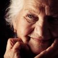 Gesicht einer freundlichen, älteren Dame, die ihrem Kopf auf eine Hand abstützt.