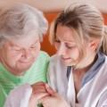 Eine Pflegekraft hält die Hand einer älteren Dame