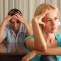 Mädchen im Vordergrund mit abwesenden Blick, Vater im Hintergrund hat Kopf in den Händen