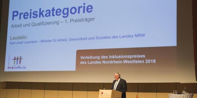 Minister Karl-Josef Laumann am Stehpult, im Hintergrund Leinwand mit Preiskategorie