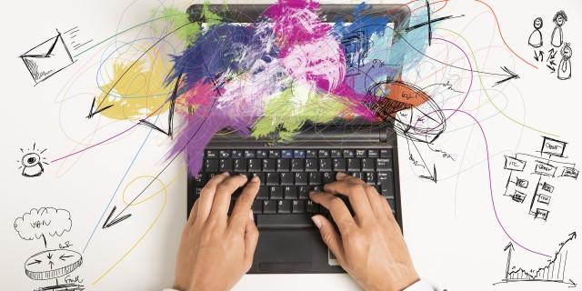 Foto: Multitasking. Businessfrau arbeitet mit Laptop, daneben Zeichnungen Jobaufgaben