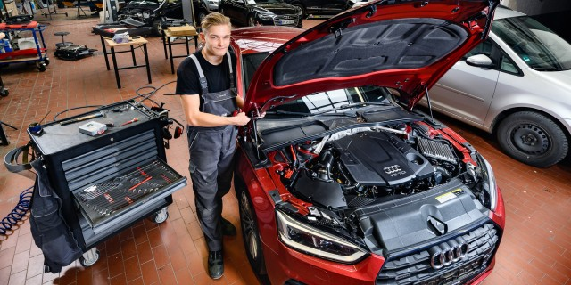Ein Azubi steht neben einem Auto in einer Werkstatt
