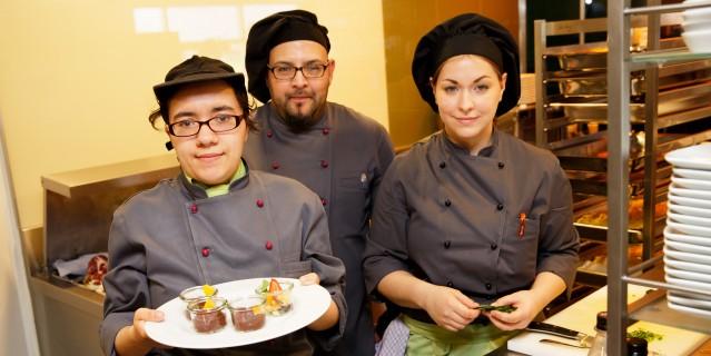 Foto: Zwei Frauen und ein Mann servieren das Essen