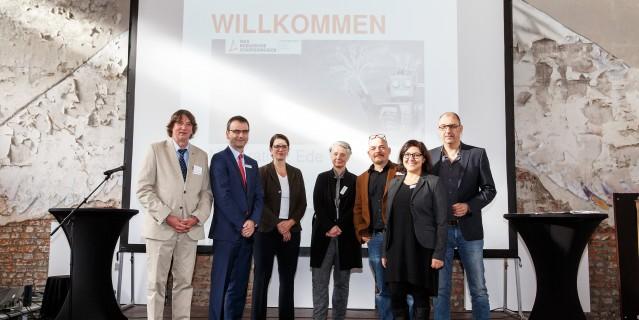 Foto: Organisator und Organisatorin, Referentinnen und Referenten sowie der Moderator auf dem Podium