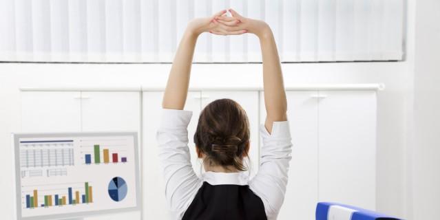 Foto zeigt eine Frau von hinten an einem Computerarbeitsplatz, die sich streckt