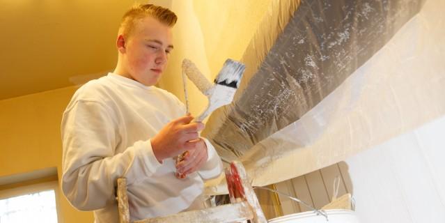Jugendlicher Auszubildender auf Leiter mit Malerpinsel