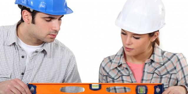 Foto: Mann und Frau, jeweils mit Bauarbeiterhelm halten gemeinsam eine Wasserwaage