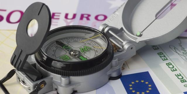 Foto: Ein Kompass liegt auf den Geldscheinen