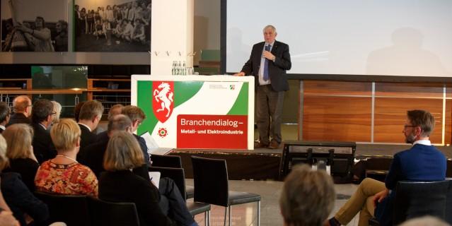 Branchendialog - Minister Laumann auf Podium mit Mikrofon