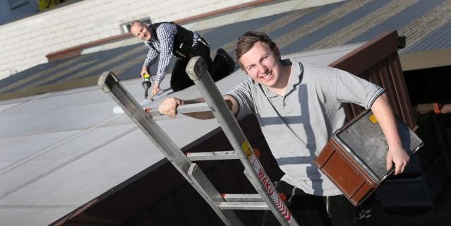 Schüler (vorne auf Leiter) und Handwerksmeister bei Dacharbeiten