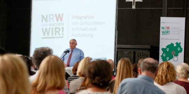 """Minister Karl-Josef Laumann am Mikrofon, im Hintergrund Logo der landesaktion """"NRW. Das machen wir!"""""""