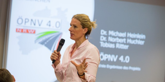 Frau mit Mikrofon, im Hintegrund Präsenationsfolie mit Veranstaltungstitel ÖPNV 4.0