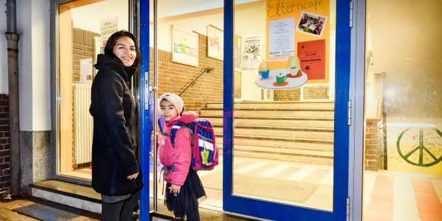 Mutter mit Tochter an Eingangstür Kinderbetreuung