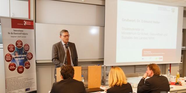 Blick in den Veranstaltungsraum, Dr. Edmund Heller neben Videoleinwand