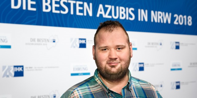 """Teilnehmer mit blauem Karo-Hemd vor Banner """"die besten Azubis in NRW 2018"""""""