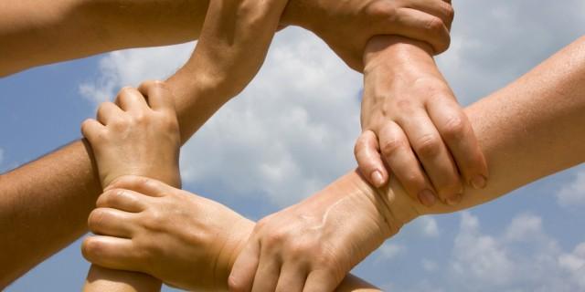 Sechs Hände greifen einander und bilden einen Kreis