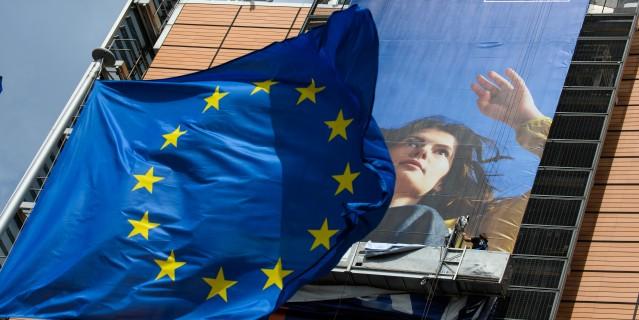 EU-Flagge und Foto werden vor dem Berlaymont-Gebäude/ Brüssel entrollt