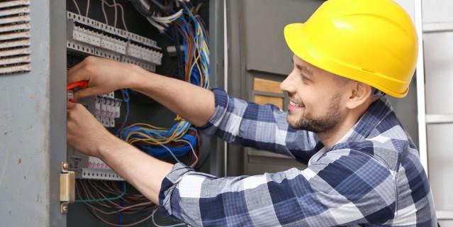 Fachkraft mit Sicherheitshelm arbeitet an Elektroleitungen