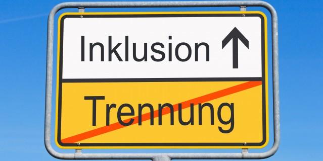 """Ein Verkehrsschild auf dem ein durchgestrichenes """"Trennung"""" und """"Inklusion"""" mit einem Pfeil nach oben steht"""
