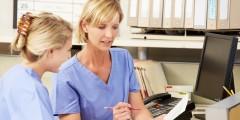 Zwei Frauen in medizinischer Arbeitskleidung sitzen an einem Schreibtisch und schauen sich ein Blatt Papier an.