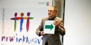 Foto: Ein Mann hält eine große Karte, wo ein grüner Pfeil abgebildet ist