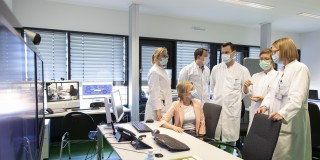 Beschäftigte im Krankenhaus in der Besprechung mit Mundschutz