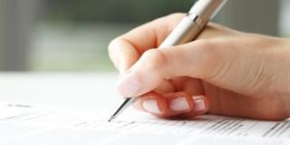 Eine Hand mit Stift, die ein Formular ausfüllt