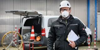 Mann mit Mundschutz und Helm, im Hintergrund Auto mit material zum Kabelverlegen