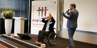 Foto: Zwei Männer singen ein Lied. Einer davon sitzt im Rollstuhl