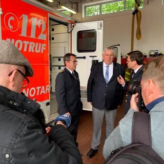 Minister Laumann steht neben einem Rettungswagen. Er ist im Gespräch mit zwei Feuerwehrleuten.