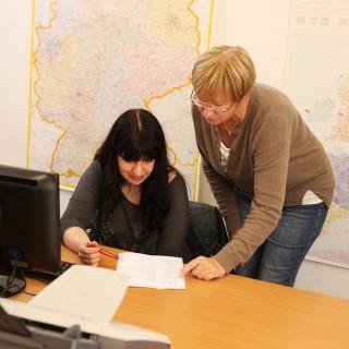 Foto: Zwei Frauen schauen sich eine Stellenanzeige an