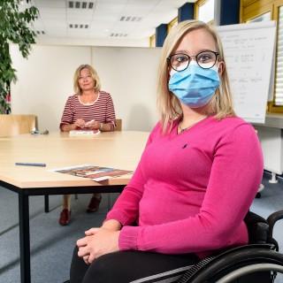 Beraterin und Auszubildende sitzen am Tisch. Die Auszubildende sitzt im Vordergrund in einem Rollstuhl