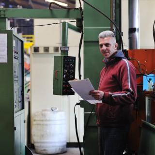 Mann steht vor einer Maschine und vergleicht etwas auf einem Zettel