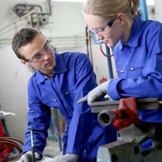 Junger Mann und junge Frau im blauen Werksanzug und Schutzbrillen
