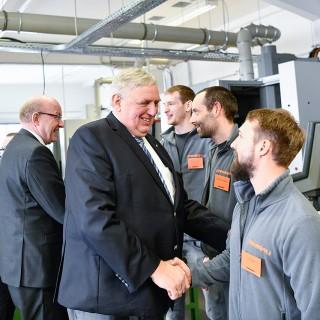 Foto: Minister begrüßt Mitarbeiter eines Unternehmens