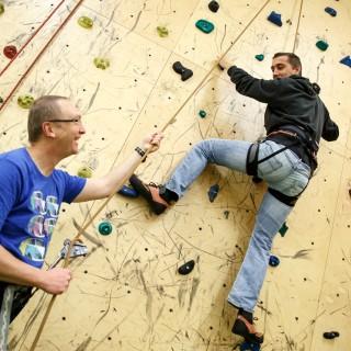Junger Mann mit Trainer an Kletterwand