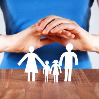 EIne Frau hält schützende Hände über eine Schrenschnittfamilie