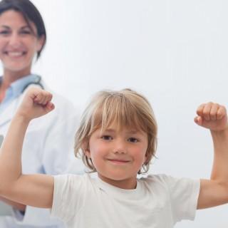 Bild zeigt kleinen Jungen, der beide Arme hoch hebt und seine Muskeln zeigt