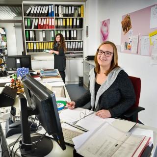 Junge Frau sitzt an Schreibtisch mit Computer und Arbeitspapieren, Kollegin am Regal im Hintergrund