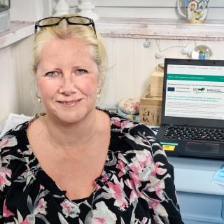Porträt Sabine Lauer, BFW Oberhausen, im Hintergrund Laptop geöffnet mit Infos zu Aktion 100