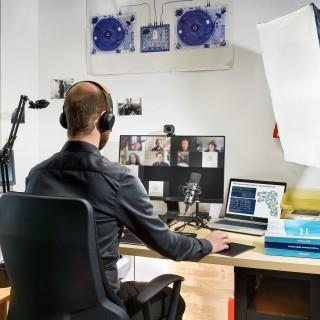 Mann mit Köpfhörer mit Sicht auf Bildschirm mit Teilnehmnden einer Webkonferenz